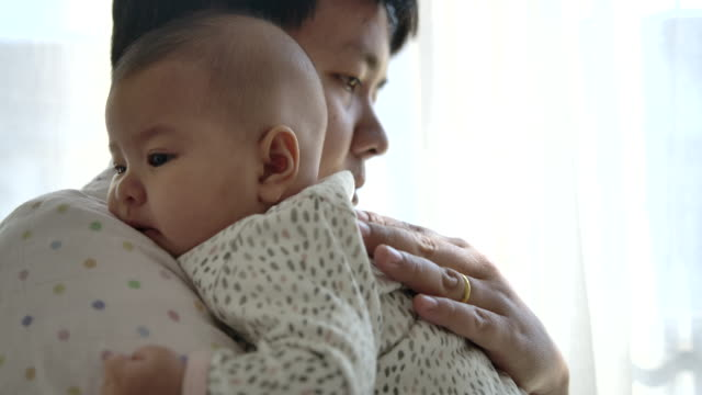 father lulled the baby to sleep by the window of the house - filipino ethnicity stock videos & royalty-free footage