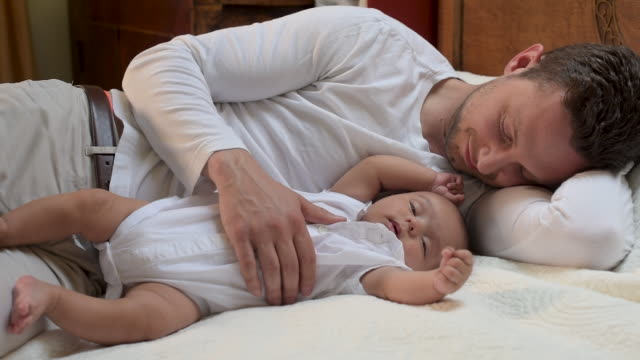 father lying beside newborn baby. - genderblend stock videos & royalty-free footage