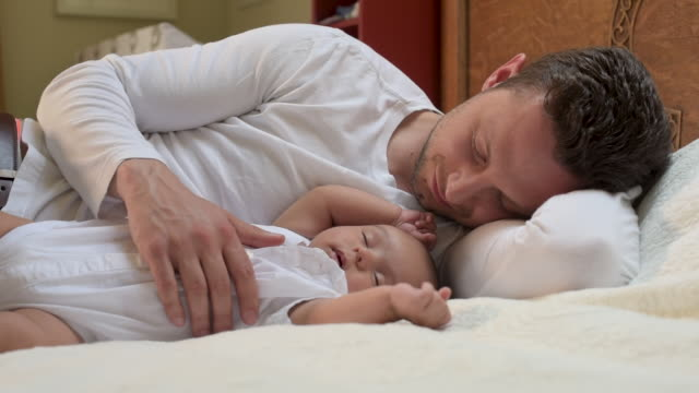 father lying beside newborn baby. - modern manhood stock videos & royalty-free footage