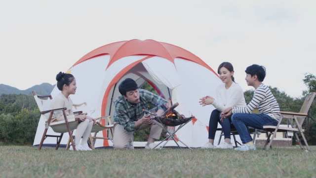 father making a fire for a family on the camping grounds - キャンプする点の映像素材/bロール