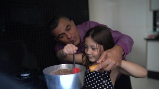 vídeos de stock, filmes e b-roll de pai fazendo chocolate com a filha em casa - 40 44 anos