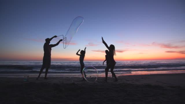 father making giant bubbles for his kids on the beach - jätte uppdiktad figur bildbanksvideor och videomaterial från bakom kulisserna