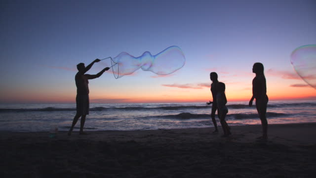 father making giant bubbles on the beach - large stock videos & royalty-free footage