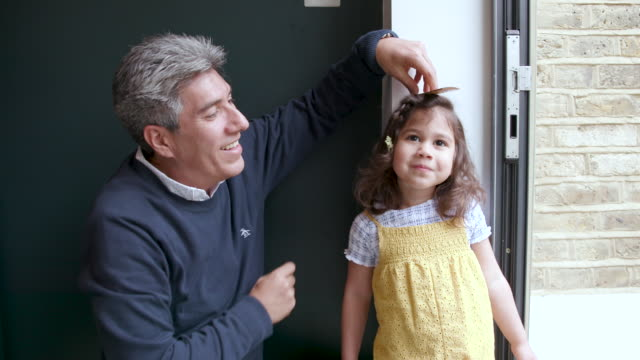 a father measures his baby daughter against a wall at home to see how tall she is - candid stock videos & royalty-free footage