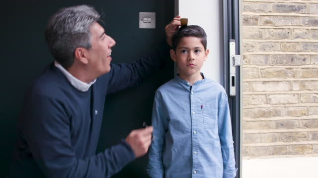 a father measures his young son against a wall to see how tall he is - instrument of measurement stock videos & royalty-free footage