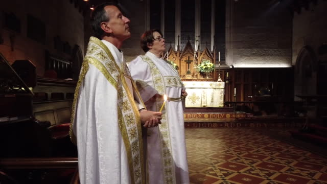father michael deasey holds a candle as father james collins and lay minister rosemary king look on during the 'blessing of the new light and paschal... - congregation stock videos & royalty-free footage