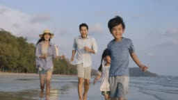 Father, Mother and children running on the beach at the day time. Slow motion. Family, Holiday and Travel concept.