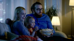 Father, Mother and Little Girl Watching TV. They Sit on a Sofa in Their Cozy Living Room and Eat Popcorn. It's Evening.