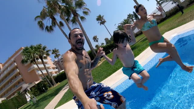 father, mother and son having fun in pool in summer - standing water stock videos & royalty-free footage