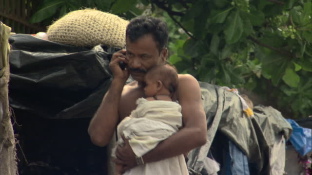 ms td father on cell phone carrying baby past shanty in slums, mumbai, maharashtra, india - slum stock videos & royalty-free footage