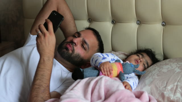 father on mobile in bed with baby - napping stock videos & royalty-free footage