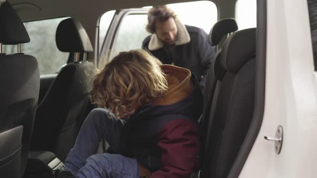 vídeos de stock e filmes b-roll de father opens car door, two young boys run and jump inside - jaqueta jeans
