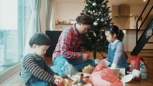vidéos et rushes de le père ouvre des cadeaux de noël avec son fils et sa fille - son