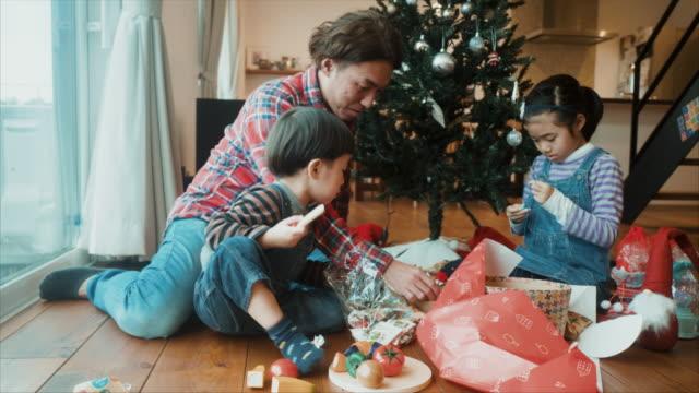 父は彼の息子と娘とクリスマスプレゼントを開きます - son点の映像素材/bロール