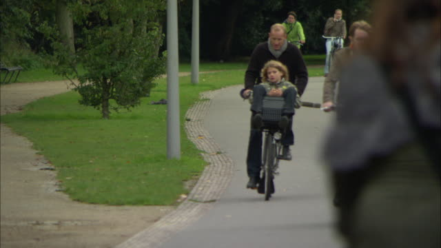 stockvideo's en b-roll-footage met ms selective focus father pedaling bike as his son sitting in milk crate attached to handlebars / amsterdam, holland - nederland