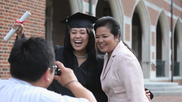 ms father photographing daughter and mother, celebrating college graduation / richmond, virginia, usa - 記念撮影点の映像素材/bロール