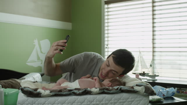 ms father photographing himself with baby boy  with phone camera in nursery / lehi, utah, usa - lehi stock-videos und b-roll-filmmaterial