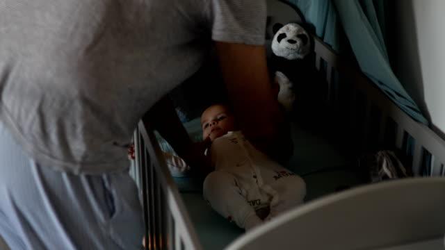 stockvideo's en b-roll-footage met vader oppakken van baby uit de wieg - genderblend