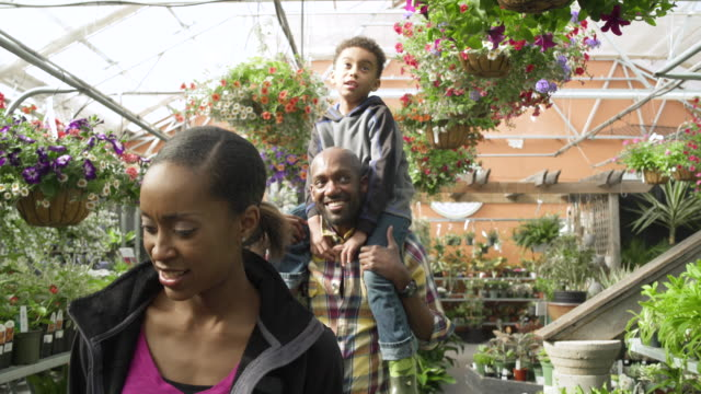 Father piggybacking his son in a greenhouse