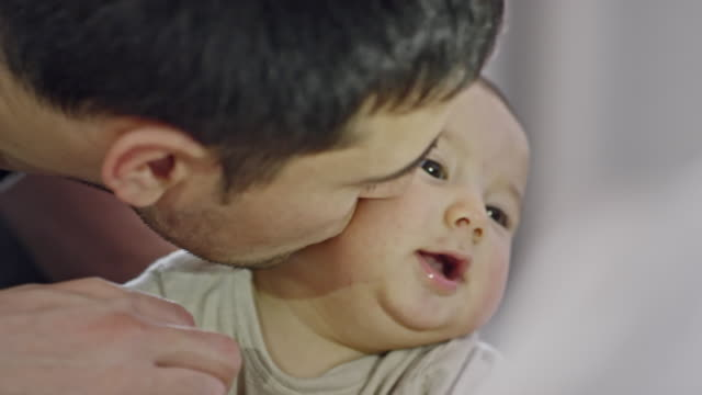 vidéos et rushes de father pinching cheek and playing with baby boy - pincer