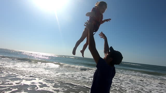 father playfully throws his daughter in the air at the beach - swimwear stock videos & royalty-free footage