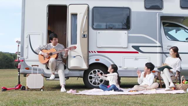 father playing a guitar for children in front of camper trailer on the camping grounds - キャンプする点の映像素材/bロール
