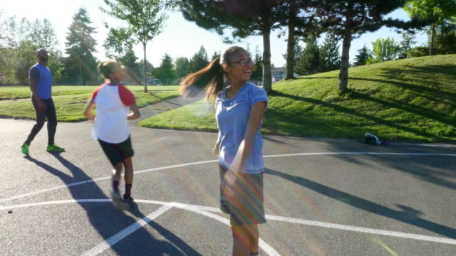 MS Father playing basketball with daughters on outdoor court on summer evening