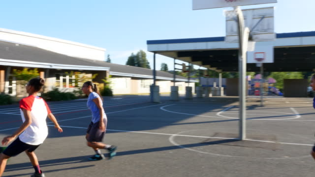 MS TS Father playing basketball with daughters on outdoor court on summer evening