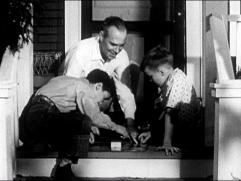 1950 Father playing board game on front stoop with two sons / USA / AUDIO