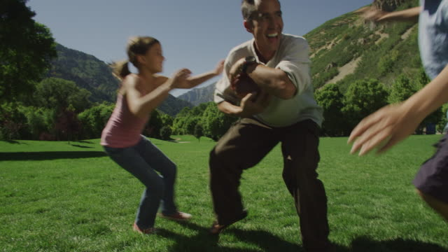 father playing football with his kids - tackling stock videos and b-roll footage