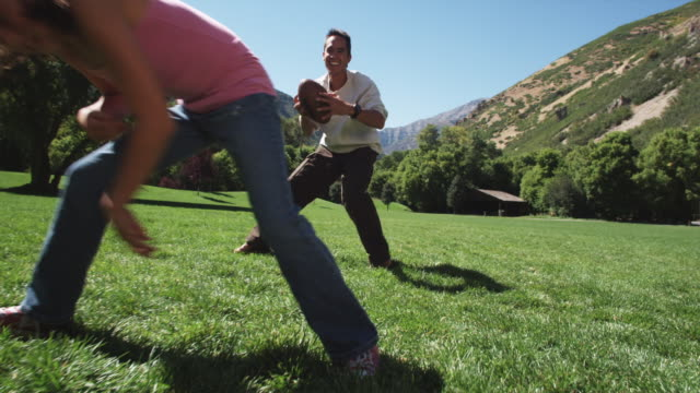 father playing football with his kids