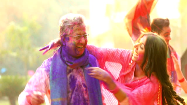vídeos y material grabado en eventos de stock de father playing holi festival with her daughter, delhi, india - holi