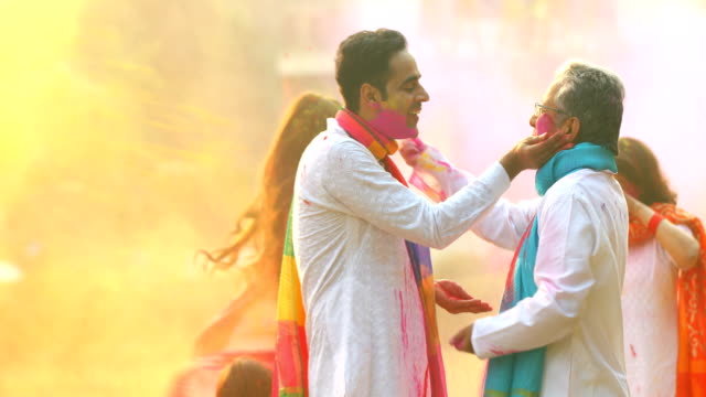 Father playing holi festival with her son, Delhi, India