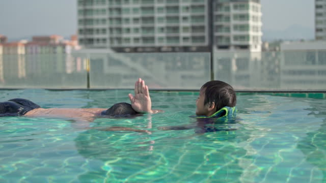 vídeos de stock e filmes b-roll de father playing role as a shark with his son in swimming pool of apartment or hotel in vacation - povo tailandês