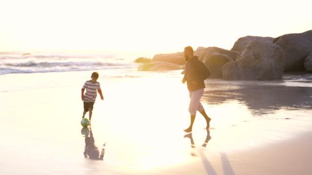 vídeos de stock e filmes b-roll de father playing soccer with his son on the beach - família com um filho