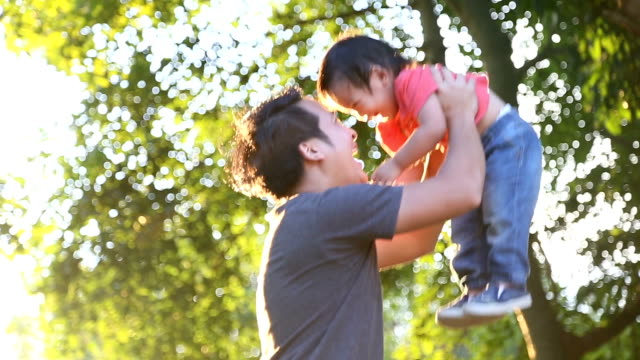 father playing with baby boy at sunset. - genderblend stock videos & royalty-free footage