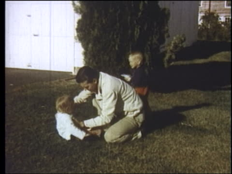 1957 father playing with children on front lawn / new jersey - 1957 stock-videos und b-roll-filmmaterial