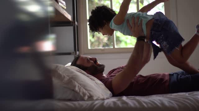 vídeos de stock, filmes e b-roll de pai brincando com a filha levantando-a no ar na cama em casa - braço humano