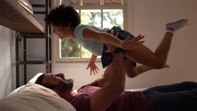 stockvideo's en b-roll-footage met het spelen van de vader met dochter die haar in de lucht in bed thuis opheft - resting
