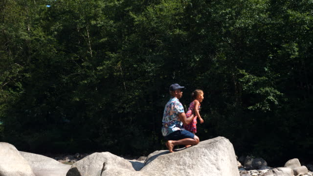 ws father playing with daughter on rock by river on summer afternoon - kneeling stock videos & royalty-free footage