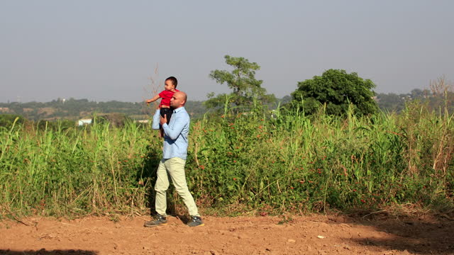 father playing with his cute little daughter outdoors in the agricultural field - sorghum stock videos & royalty-free footage