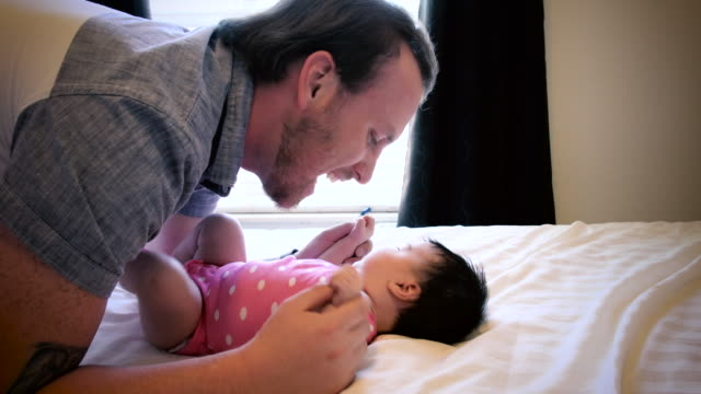 father playing with infant daughter on bed - hugging self stock videos & royalty-free footage