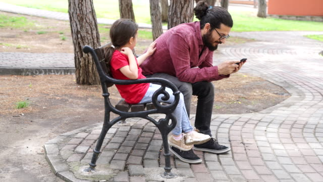 father playing with phone while his daughter gets bored - addiction stock videos and b-roll footage