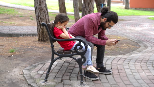 father playing with phone while his daughter gets bored - dependency stock videos & royalty-free footage