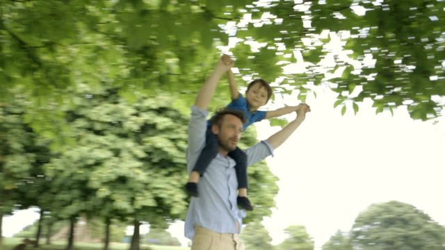 father playing with son in park. - 肩車点の映像素材/bロール
