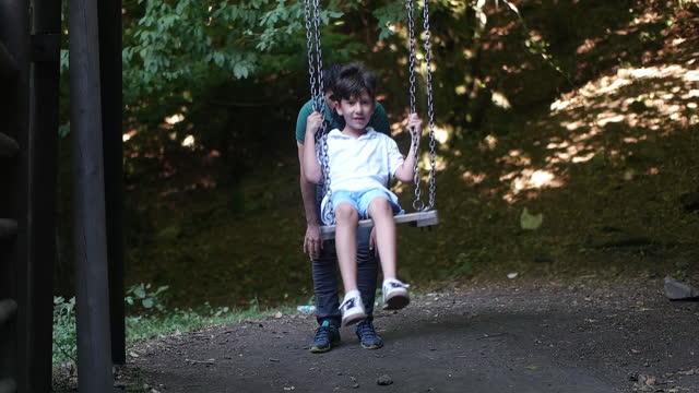 息子のスイングで遊んでいる父 - 自閉症点の映像素材/bロール