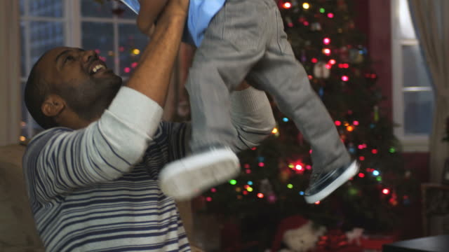 ms pan father playing with toddler with xmas tree in background  / newark, new jersey, usa - genderblend stock videos & royalty-free footage