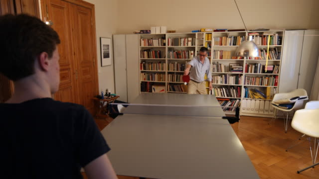 a father plays table tennis with his son in his flat where he has built up a table tennis table on march 27 2020 in berlin germany everyday life in... - table tennis stock videos & royalty-free footage