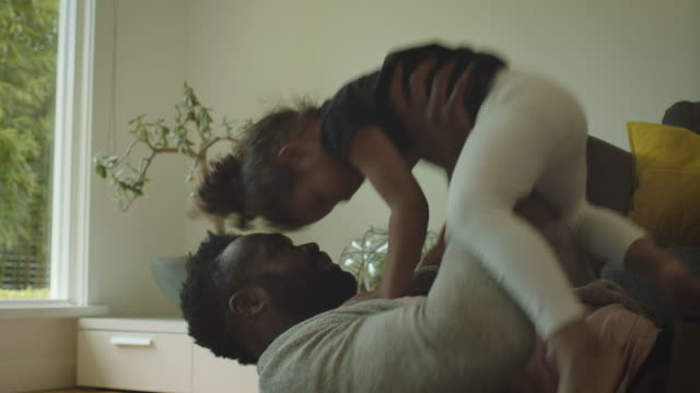 Father plays with daughter on the floor in the living room at home