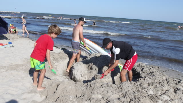 vidéos et rushes de father plays with his son and builds together with another father a sandcastle at the baltic sea while people relax at the beach at high summer... - chapeau de soleil